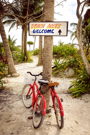 shore: Tranquil scene with two bicycles, beach, palms and welcome sign Stock Photo
