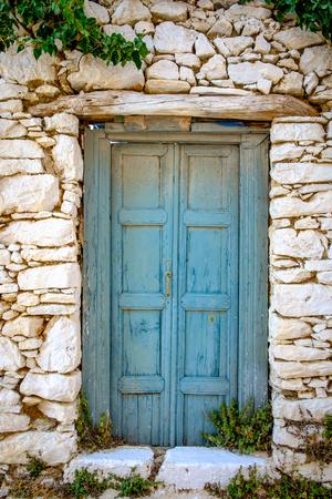 Détail de bleu coloré porte en bois dans le mur en pierre vintage, Grèce