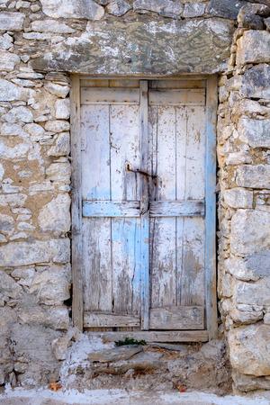 Old wooden door in stone wall in vintage style, Greece Standard-Bild