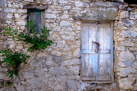 Old wooden door and window in stone wall in vintage style, Greece Standard-Bild