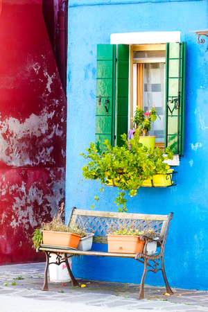window bench: Colorful houses, window with flowers and bench on Burano, Venice, Italy Stock Photo