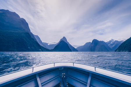 Milford Sound cliffs and mountains in cold blue tone viewed from the boat, New Zealand
