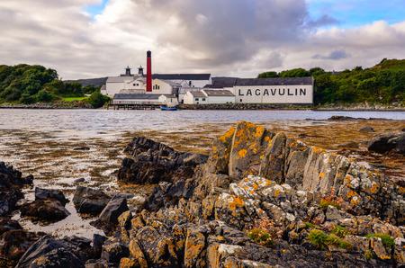 ISLAY, UNITED KINGDOM - 25 August 2013: Lagavulin distillery factory with ocean coastline foreground, Islay, United Kingdom