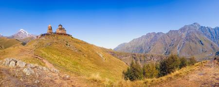 Panoramic view of Kazbegi mountain range and Tsminda Sameba church, Country of Georgia Stock Photo