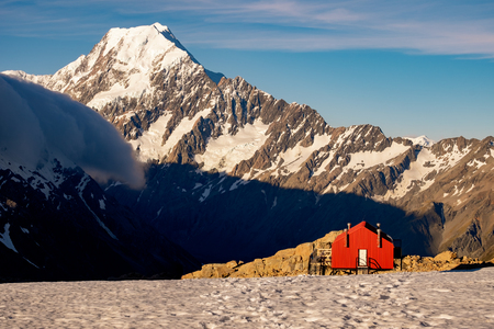 Red mountain hut and Mt Cook in the background, South Island, New Zealand 免版税图像