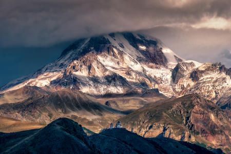 Dramatic landscape view of Mt Kazbeg and Tsminda Sameba church, Caucasus mountains, Country of Georgia