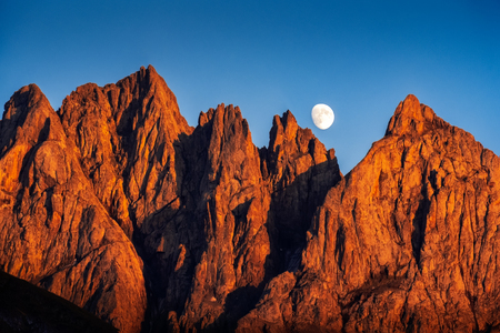 Landscape view of beautiful colorful mountain peaks at sunset with rising moon