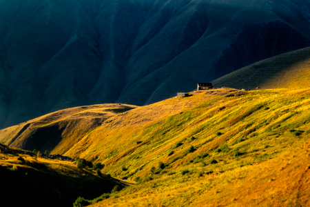 Colorful sunset with mountain meadows and hut in Caucasus, Kazbegi national park, Country of Georgia