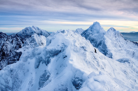 Beautiful winter landscape with lonely climber and snowed mountain peaks, High Tatras, Slovakia 免版税图像