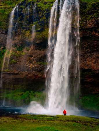 Landscape view of beautiful waterfall and person in red jacket, Iceland, Europe Zdjęcie Seryjne