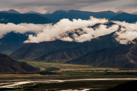 Dark moody landscape view of mountains and hills in Tibet, Asia 免版税图像