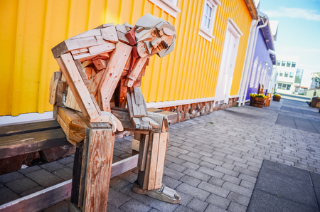 SIGLUFJORDUR, ICELAND - 15 August 2012: Sitting wooden statue with colorful background in Siglufjordur, Iceland Publikacyjne
