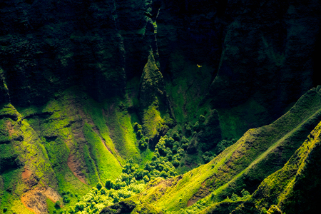 Landscape detail of Na Pali coast cliffs with helicopter in distance, Kauai, Hawaii, USA