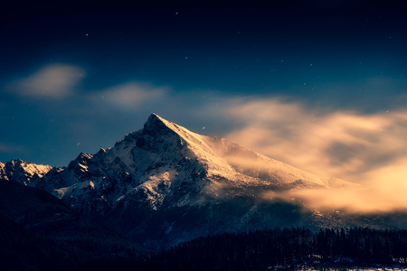 Night time landscape view of mountain peak Krivan with moonlight and clouds, High Tatras, Slovakia, Europe