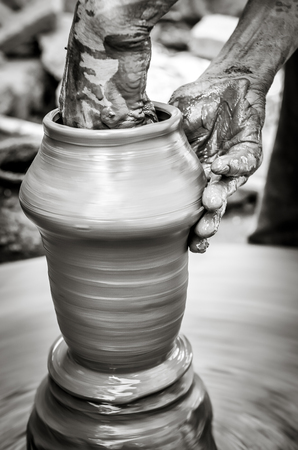 Hands of a man creating pottery on wheel, monochrome vintage style view
