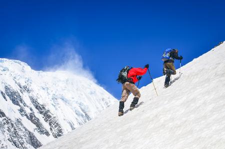 Deux randonneurs de montagne marchant sur une colline escarpée avec fond de sommets enneigés, Himalaya