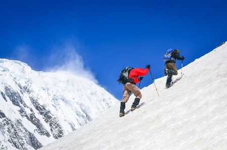 Two mountain backpackers walking on steep hill with snowed peaks background, Himalayas Stock Photo