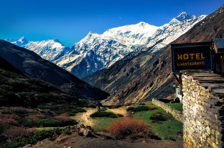 Mountain landscape view with local stone hut and hotel sign, Himalayas, Nepal