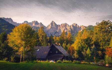 Landscape view of mountain peaks, colorful autumn foliage and cottage, Triglav national park, Slovenia, Europe