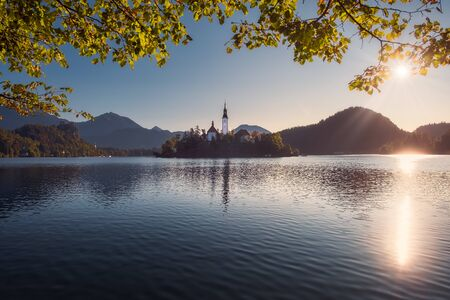 Scenic view of Lake Bled and island with church, colorful autumn foliage, Slovenia, Europe