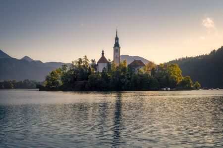 Scenic view of Lake Bled island with church and colorful autumn foliage, Slovenia, Europe 免版税图像 - 135032095