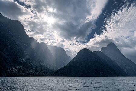Scenic view of Milford Sound mountains with dramatic clouds and sunrays, South Island, New Zealand 免版税图像 - 136550169