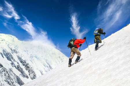 Two mountain trekkers on steep snowed hill with dramatic sky background, Himalayas, Nepal