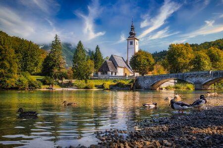 Scenic view of Lake Bohinj church with beautiful colorful foliage, Slovenia, Europe 免版税图像 - 140358057