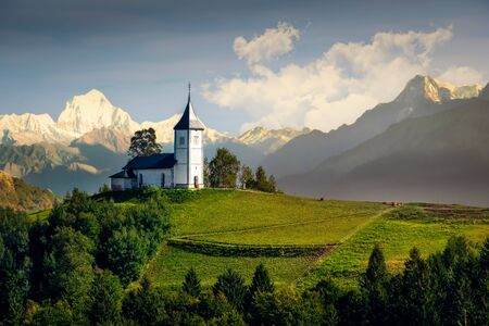 Landscape view of Jamnik church and generic mountains - composite image, Slovenia, Europe 免版税图像 - 143134040