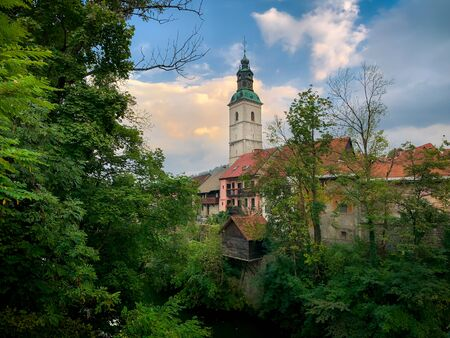 Scenic view of Skofja loka church and old houses with green foliage, Slovenia, Europe
