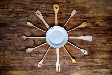 Detail of wooden cooking spoons in shape of a clock on textured table, vintage style 免版税图像