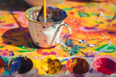 Detail view of messy painting colours and painter's cup with paintbrush on a colorful canvas