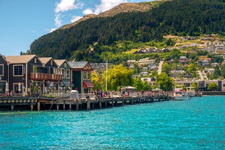 QUEENSTOWN, NEW ZEALAND - 13 JANUARY 2017: Scenic view of lake, street houses and tourists enjoying beautiful sunny day, Queenstown, New Zealand