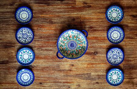 Detail of painted ornate pottery plates on wooden textured table, vintage style