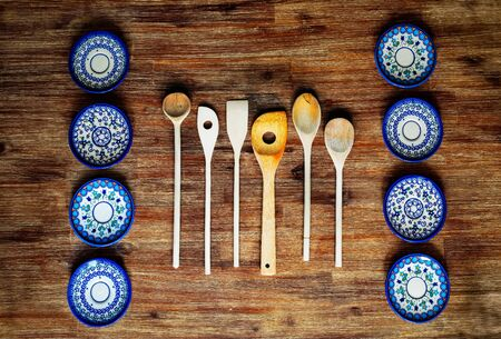 Detail of wooden cooking spoons and painted ornate plates on textured wooden table in vintage style 免版税图像