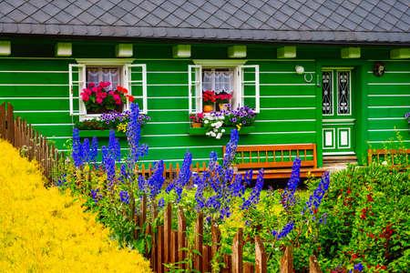 Architectural detail of vibrant colorful cottage wall and windows with blooming flowers 免版税图像