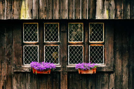 Detail of old vintage wooden wall with rusty windows and flowers