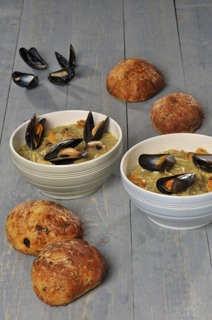 layman: mussel soup in a bowl with cheese bread and mussel shells