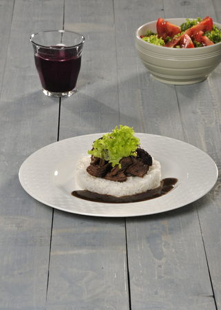 stewing: Stewing with rice and gravy served on a plate with a glass of red wine and lettuce