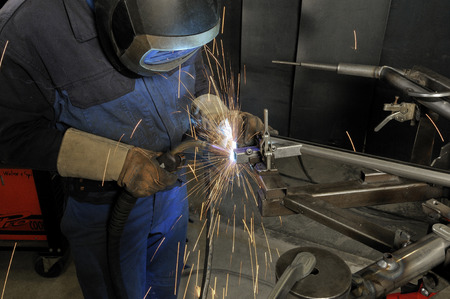 welder with protective cap at work Stock Photo