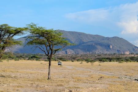 Safari Vehicle against a Mountain Background, Shaba Game Reserve, Kenya Stock Photo