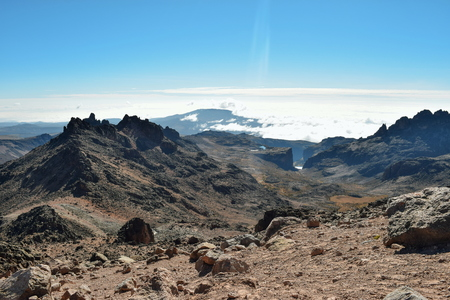 A group of hikers above the clouds at the volcanic rock formations of Mount Kenya