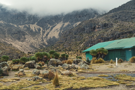 A cabin against a foggy mountain background, Mount Kenya
