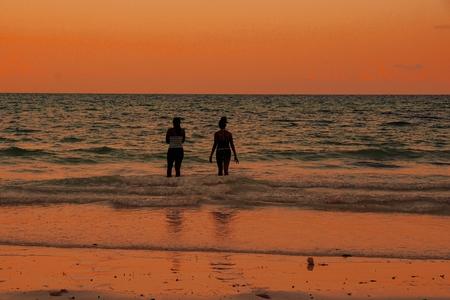 Having fun at the beach against a golden sky, Zanzibar