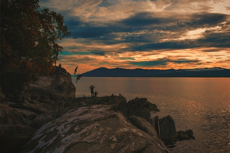 Cliff diving against a golden sunset at Kande Beach, Lake Malawi