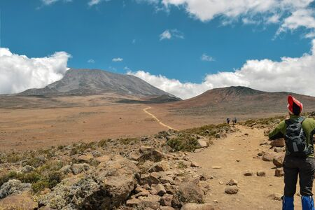 A young woman hiking against the background of Mount Kilimanjaro, Tanzanai