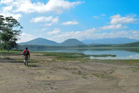 A young adult hiking along a scenic lake against a mountain background, Lake Elementaita, Naivasha, Kenya Stock Photo