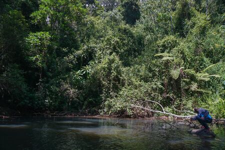 A hiker in the fresh water river in Aberdare Ranges, Kenya Stock Photo