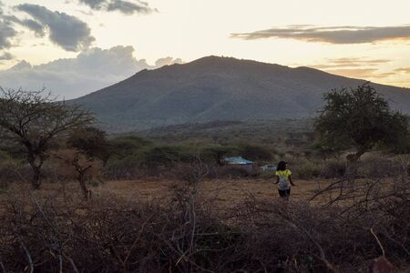 A female hiker against a amountain in the evening in rural Kenya, Kajiado County