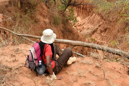 A female hiker at the top of a mountain overlooking a valley, Makueni, Kenya